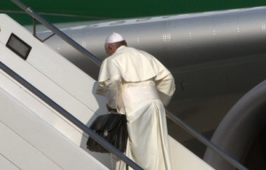 Pope Francis carrying his own bags while boarding the plane for Brazil.